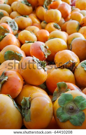 Pile of orange green topped persimmons at the farmers market - stock photo