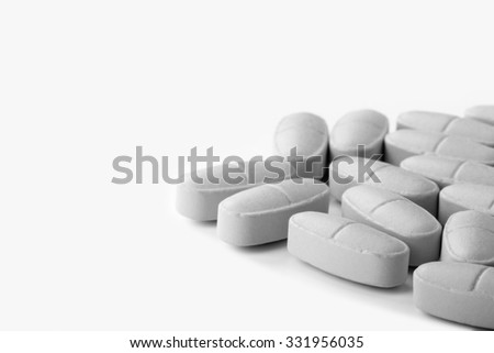 Pile of orange pills on a light background. Toned.