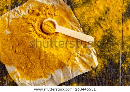 Pile of organic turmeric (curcuma) powder sitting on brown paper with measuring spoon on wooden table - stock photo