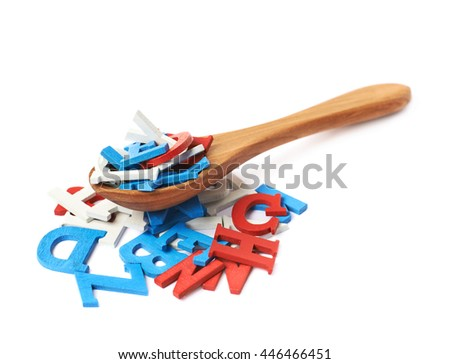 Pile of painted red, blue and white wooden letters with the wooden serving spoon over it, composition isolated over the white background - stock photo