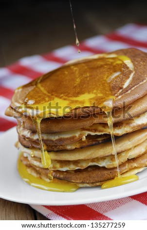 Pile of pancakes in the white plate on the wooden table