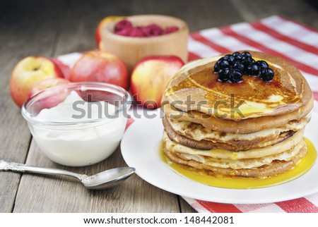 Pile of pancakes with berries in the white plate on the wooden table - stock photo