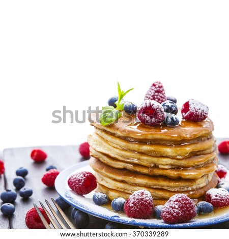 Pile of pancakes with blueberries and raspberries sprinkled with icing sugar and poured on with honey for breakfast on wooden table over white background - stock photo