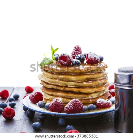 Pile of pancakes with blueberries and raspberries sprinkled with icing sugar and poured on with honey for breakfast on wooden table over white background