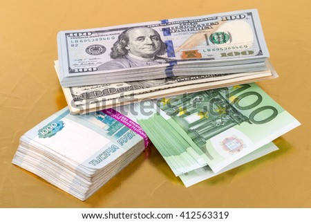 Pile of paper money (dollars, euros, russian roubles) on a gold background - stock photo