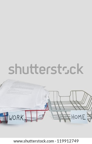 Pile of papers in work tray with empty home platter over white background - stock photo