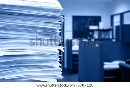 Pile of papers on a background of office cubicles.  Selective focus at the corner of the papers.  Blue tint - stock photo