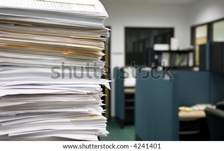 Pile of papers on a background of office cubicles.  Selective focus at the corner of the papers - stock photo