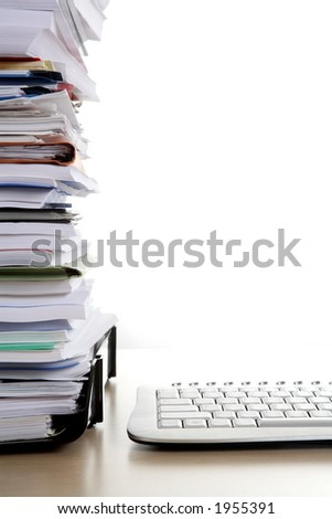Pile of paperwork next to a keyboard