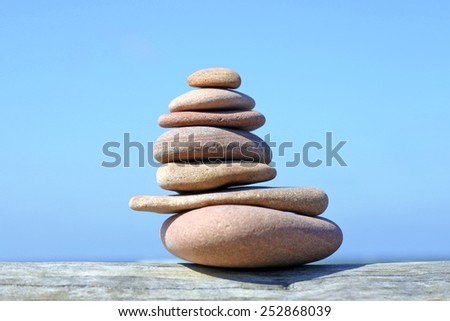 Pile of pebble stones against clear blue sky - stock photo