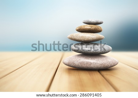 Pile of pebble stones for oriental spa massage therapy and alternative medicine on wooden planks outdoor with selective focus effect - stock photo