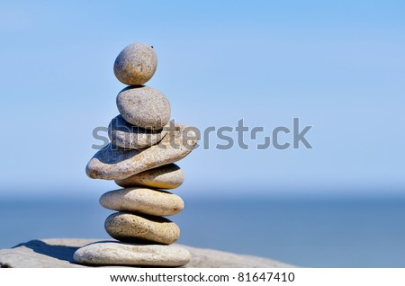 Pile of pebbles in the balance on the seacoast - stock photo