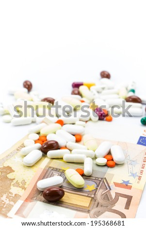 Pile of pills and banknotes closeup with copy-space  - stock photo