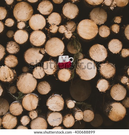 pile of pine tree trunks with little red mug