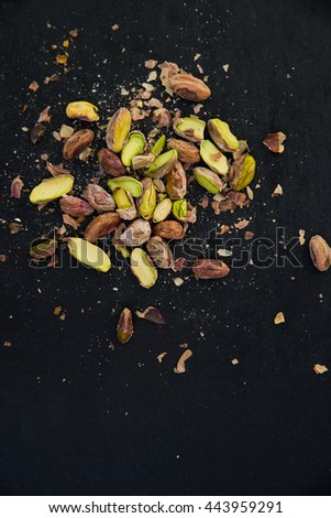 pile of pistachios on a black slate surface - stock photo