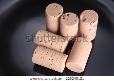 Pile of plain wine corks on a black background - stock photo