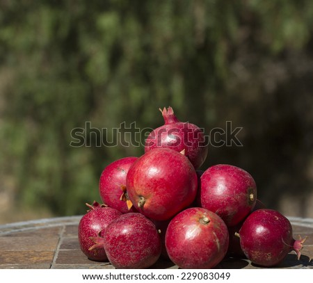 pile of pomegranates on tiled table against blurred background - stock photo