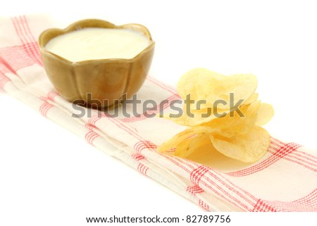 Pile of potato chips with cream sauce isolated on white background - stock photo