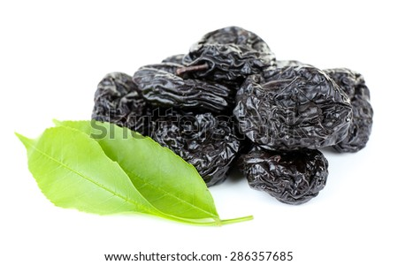 Pile of prunes with green leaves isolated on white - stock photo