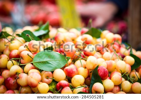 Pile of Rainier cherries with a leaf.  Other produce and signage out of focus in the background.