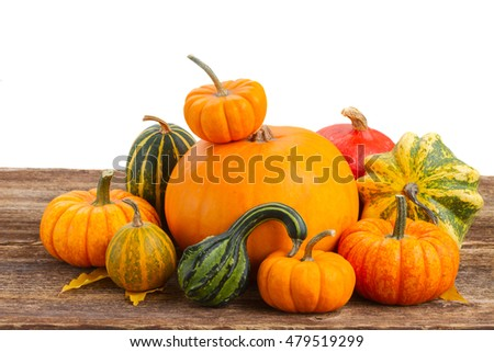 pile of raw orange pumpkins with fall leaves on wooden table isolated on white background