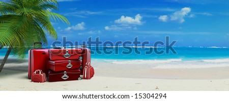 Pile of  red baggage on a tropical beach - stock photo