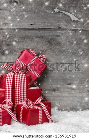 Pile of red Christmas presents, with snow on grey wooden background - stock photo