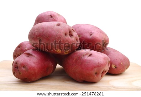 Pile of red potatoes isolated on wooden board on white background  - stock photo