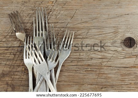 Pile of retro aluminum forks on wooden table.  - stock photo