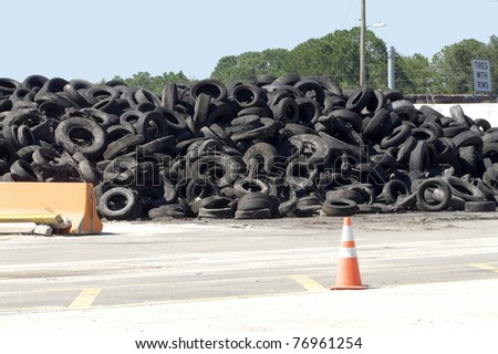 "Pile of rimless tires on ""Recycle Alley"" at a landfill. The sign for tires with rims can be seen. - stock photo"