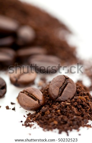 Pile of roasted and ground brown coffee beans isolated on white background - stock photo