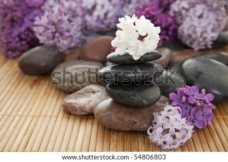 Pile of rocks with flowers on a bamboo mat. Focus on white flower on top of stack. - stock photo