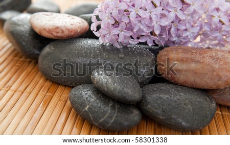 Pile of rocks with lilacs and stones on a bamboo mat.