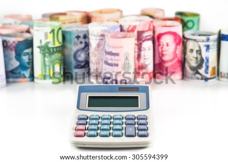 Pile of rolled-up currency notes with a calculator in foreground. - stock photo