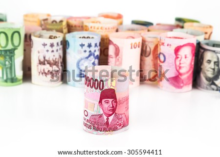 Pile of rolled-up currency notes with Indonesia Rupiah in front. - stock photo