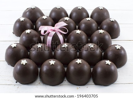 Pile of round chocolate candies and one candy with pink bow - stock photo