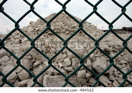 Pile of rubble from demolished building viewed through a fence - stock photo