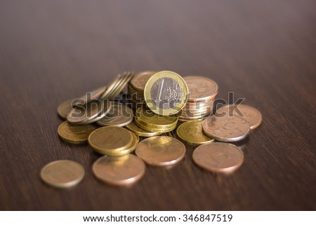 pile of russian coins on a wooden background with the euro in the middle