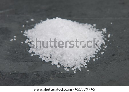 Pile of salt on a grey slate table, stock picture