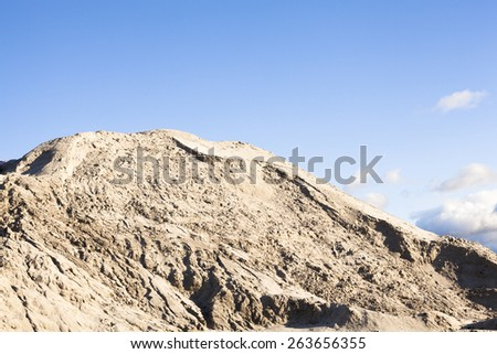 Pile of sand and blue sky over it. - stock photo