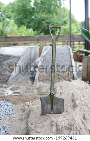 Pile of sand and shovel for construction
