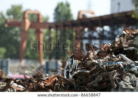 Pile of scrap iron and crane. Blurred background - stock photo