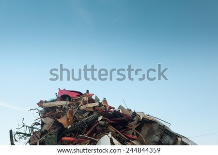 pile of scrap metal at recycling center, with clear blue sky - stock photo