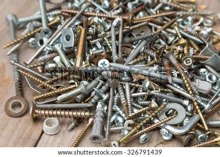 Pile of screws and nails on wooden bench - stock photo