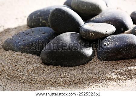 Pile of sea pebbles on shiny sand background - stock photo