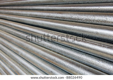 Pile of shiny galvanized steel pipe diminishing from right to left - stock photo