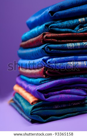 Pile of silk fabric of different color with beautiful ornament