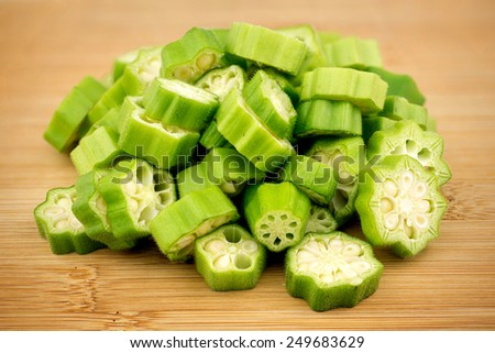 Pile of sliced okra bhindi pieces on rustic wooden background - stock photo