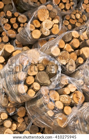 Pile of small firewood bundles, wrapped in foil; Sale of firewood;  - stock photo