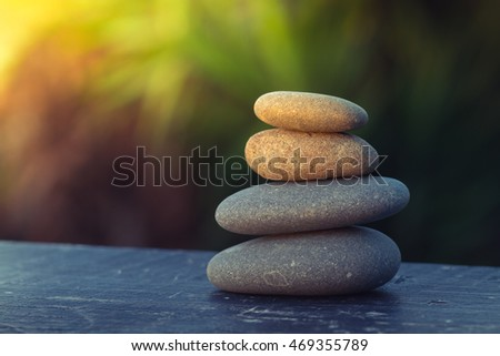 pile of smooth round pebbles balanced on top of  an old plank,  with an out of focus background for copy space and sun flare coming from the top left corner.